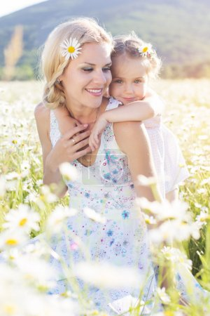Family mother and daughter in a field of daisy flowers