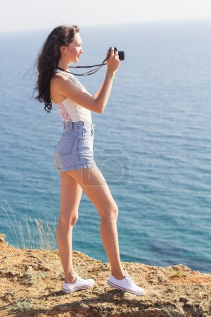 Photographer girl making pictures by old camera on mountain top