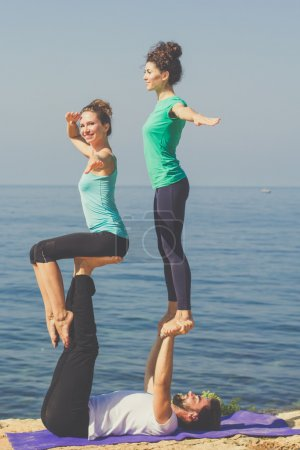Sportive three persons are doing acroyoga on the beach