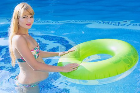 Pregnant woman is swimming with green rubber ring in pool