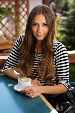 Photo for Young fashion woman drinking coffee  in a cafe outdoors. Summer time - Royalty Free Image