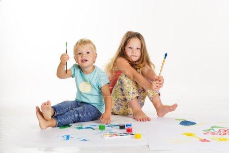 Photo pour Deux jolis enfants amis garçon et fille dessinent des photos par des peintures - image libre de droit