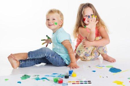 Photo pour Deux garçons et filles heureux s'amusent et dessinent des photos avec des peintures aquarelle, isolées sur du blanc, prises en studio - image libre de droit