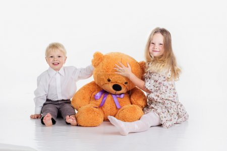 Children are sitting with big teddy bear