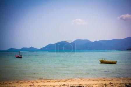 Boats on sand beach overlooking island