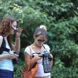 Постер, плакат: Women photographers taking photo in jungle