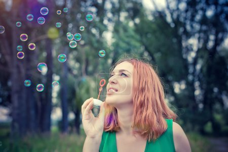 Photo for Romantic beautiful young smiles woman blowing soap balloons in a flower meadow. Slowmotion. 1920x1080 - Royalty Free Image