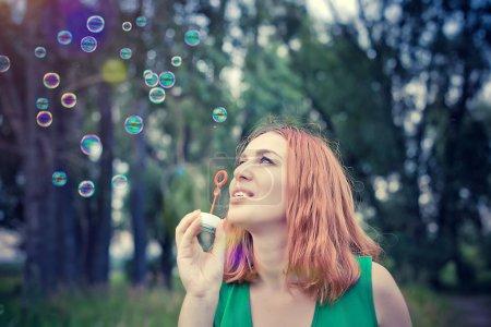 Photo pour Romantique belle jeune femme sourit soufflant des ballons de savon dans une prairie de fleurs. Au ralenti. 1920x1080 - image libre de droit