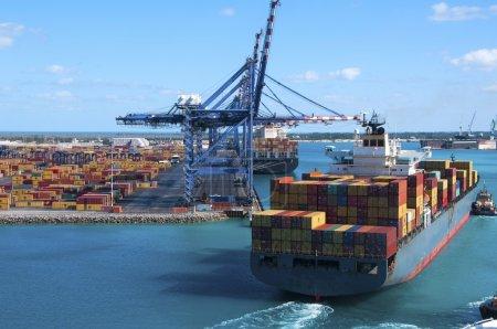 Photo pour Port de Freeport Bahamas Chantier naval à conteneurs avec grues à levage lourd et un navire entrant à quai assisté par des remorqueurs - image libre de droit