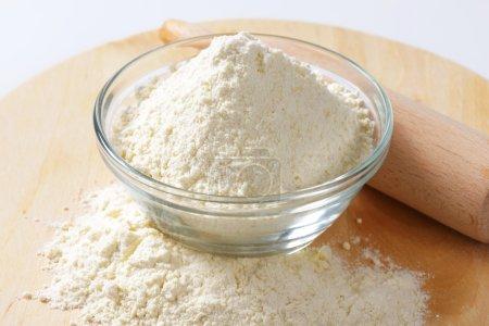 Photo pour Bol de farine et rouleau à pâtisserie sur une planche de bois - image libre de droit