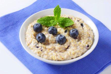 Photo pour Bol de bouillie d'avoine à grains entiers aux bleuets - image libre de droit