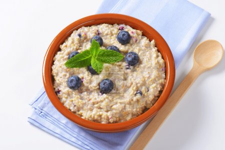 Photo for Bowl of whole grain oat porridge with blueberries - Royalty Free Image