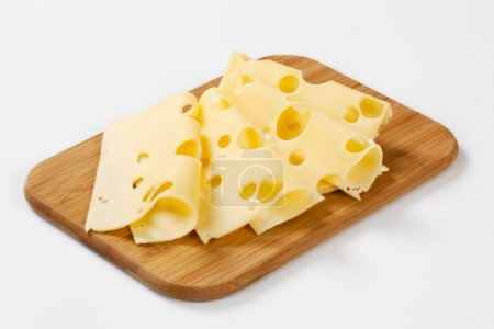 Photo for Thin slices of emmental cheese on wooden cutting board - Royalty Free Image
