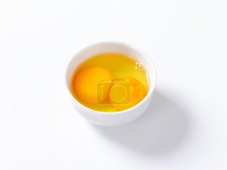 Fresh egg whites and yolks in white bowl...