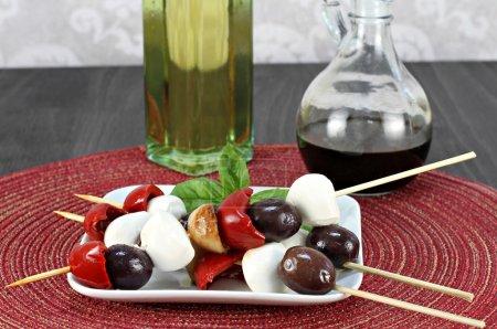 Photo pour Antipasto sur une brochette. Les brochettes comprennent des olives italiennes, des poivrons rôtis et de l'ail avec du fromage mozzarella . - image libre de droit
