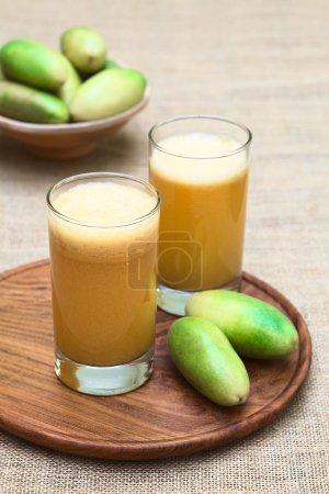 Photo pour Jus frais à base de fruits latino-américains appelés fruits de la passion banane (lat. Passiflora tripartita) (en espagnol principalement tumbo, curuba, taxo) (Selective Focus, Focus sur le devant du premier verre) - image libre de droit