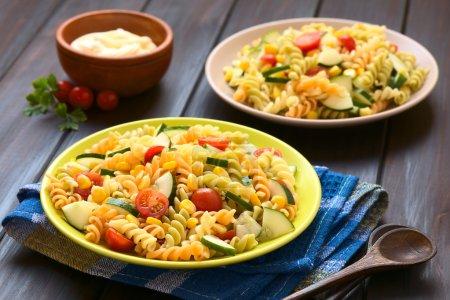 Photo pour Deux assiettes de salade de pâtes végétariennes à base de fusilli tricolore, maïs sucré, concombre et tomate cerise avec mayonnaise à l'arrière, photographiées avec une lumière naturelle (Selective Focus, Focus un tiers dans la première salade) - image libre de droit