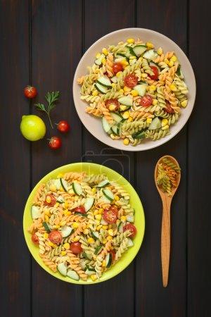 Photo pour Coup de tête de deux assiettes de salade de pâtes végétariennes en fusilli tricolore, maïs sucré, concombre et tomate cerise, photographié sur bois foncé avec la lumière naturelle - image libre de droit