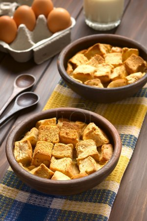 Two rustic bowls of bread pudding made of diced st...