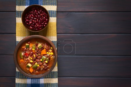 Photo for Overhead shot of a rustic bowl of vegetarian chili dish made with kidney bean, carrot, zucchini, bell pepper, sweet corn, tomato, onion, garlic, raw kidney beans in bowl above, photographed on dark wood with natural light - Royalty Free Image