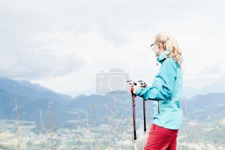 Foto de Mujer con gafas y ropa al aire libre (rígido impermeable chaqueta softshell pantalones y), de pie con bastones de trekking en las manos durante el senderismo pista en Alpes bávaros - concepto de estilo de vida saludable - Imagen libre de derechos