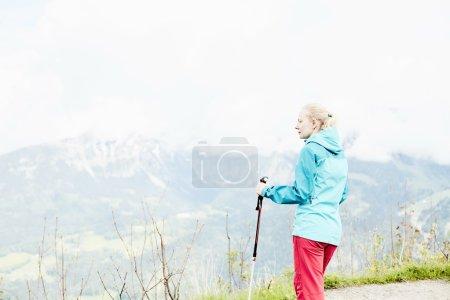 Foto de Mujer con cola de caballo la ropa al aire libre (rígido impermeable chaqueta softshell pantalones y), pista de pie con bastones de trekking en las manos durante el trekking en Alpes bávaros - concepto de estilo de vida saludable - Imagen libre de derechos