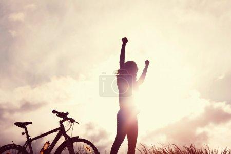 Photo pour Portrait tonique de jeune femme avec les mains levées sur les rayons de soleil - image libre de droit