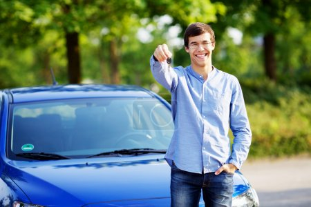 Photo for Happy young man in glasses standing in front of his new car and showing car key - Royalty Free Image