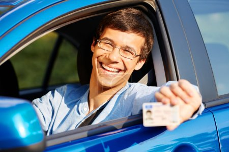 Photo for Happy young man in glasses showing his driving license from open car window - Royalty Free Image