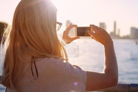 Photo pour Gros plan de fille blonde dans des lunettes prenant des photos de la baie de la ville avec téléphone mobile au coucher du soleil. Focus sur les lunettes - image libre de droit