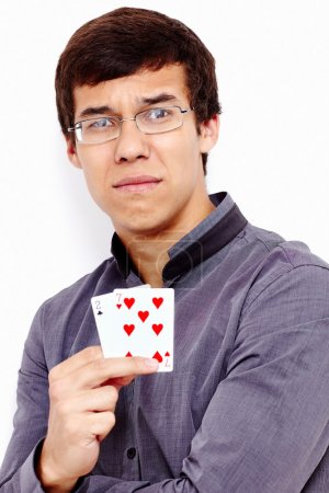 Photo for Close up portrait of young disappointed hispanic man wearing grey shirt holding 2-7 (worst standard poker starting hand) in his hand against white wall - gambling failing concept - Royalty Free Image
