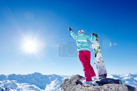 Snowboarder with raised hand in mountains