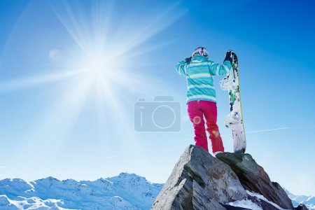 Snowboarder looking to mountains