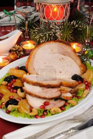 Photo pour Tranches de jambon de dinde cuit au four avec garniture de fruits sur la table de Noël - image libre de droit