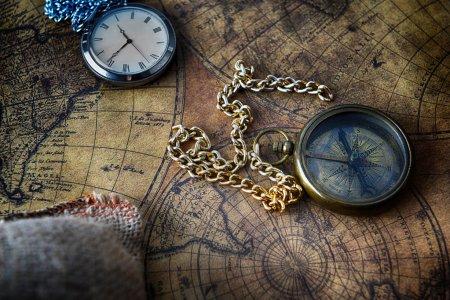 Photo pour Vintage boussole et une montre de poche couché sur l'ancienne carte - image libre de droit