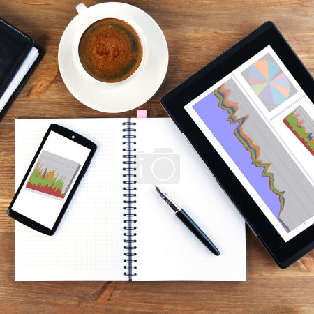 Photo pour Carnet ouvert, téléphone portable, stylo et tasse de café - image libre de droit