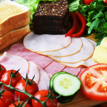 Photo for Big group of meat, cheese, bread and vegetables on a wooden table - Royalty Free Image