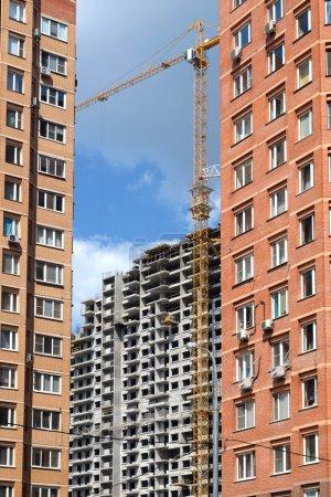 Photo pour Construction du quartier de la ville. Construction de maisons en brique au premier plan et construction de bâtiments en béton à l'arrière-plan. Photo en journée ensoleillée vue verticale - image libre de droit