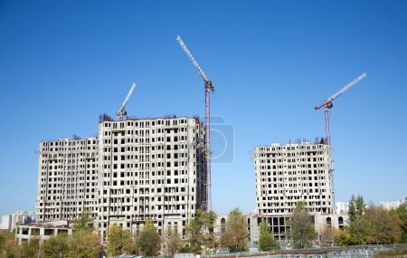 Big hoisting tower cranes and top section of moder...
