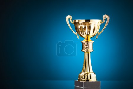 Gold cup trophy on blue background