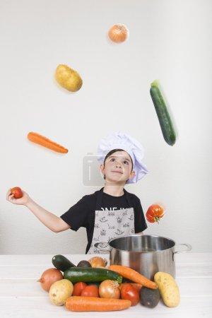 Photo pour Cuisine d'enfant avec des légumes qui les font voler - image libre de droit