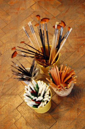 Pencils and brushes on wooden floor