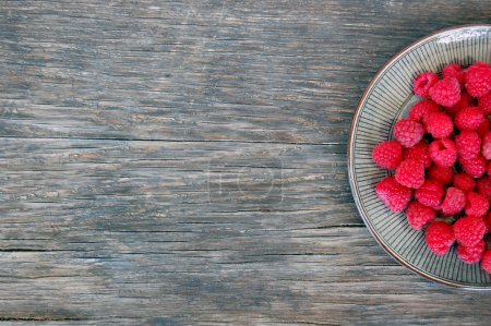 Raspberries on rustic wooden table
