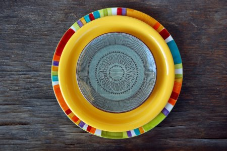 Colorful plates on wooden background