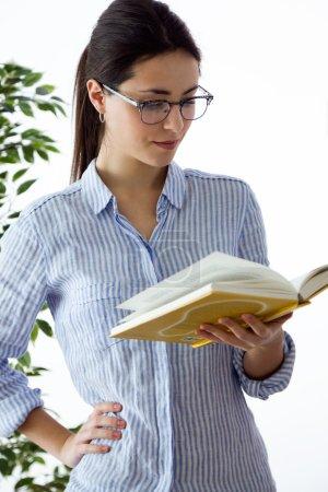 hermosa joven leyendo un libro en casa