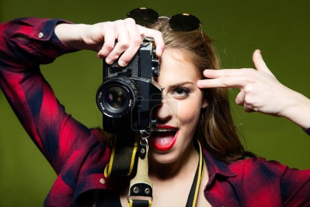 Pretty young woman taking photos with a retro camera.