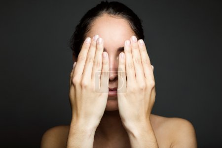 Young woman covering half of her face with a hand.