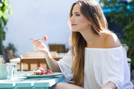 Beautiful young woman eating salad in the home garden.