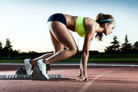 Photo for Portrait of young female athlete launching off the start line in a race. - Royalty Free Image