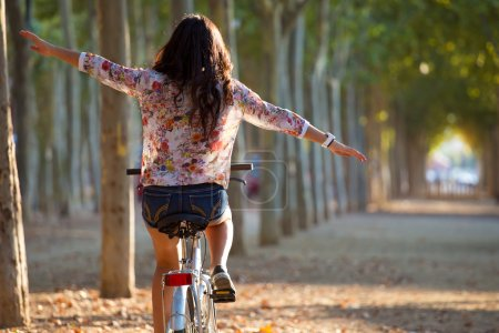 Photo for Outdoor portrait of pretty young girl riding bike in a forest. - Royalty Free Image